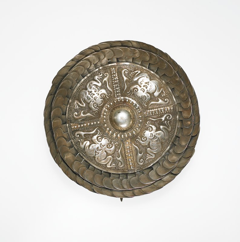 ornamental disk with sphere in the center; four panels, each decorated with a frog, surround the sphere; two layers of +-shaped fringe run around the disk; long pin on back of disk is attached at the center