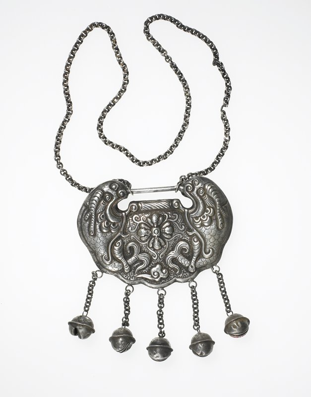 semi-circular pendant with relief motifs including fish or fish-like shapes on either side, central floral motif; upper fish-like motifs joined by a bar to which chain is attached; five pendant bells attached by chains; hollow; design on both sides
