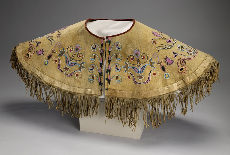 short hide cape with hook at neck and bottom fringe; brown cloth trim at neckline, blue silk trim at front opening; scrolling organic foliate design beadwork with four stars separating foliate motifs; multicolored beads with slight predominance of pink beads