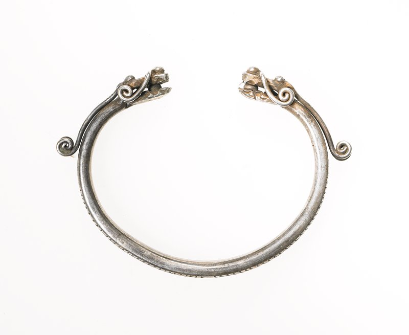one of a pair of bracelets; loop of thick, silver wire; wire has flower and vine pattern etched on it; ends of loop have dragon heads on them; dragons have spheres between their jaws; long antennas and whiskers end in curlicues