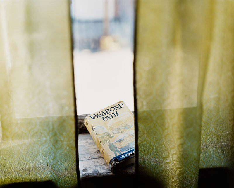 "green curtains; worn book with paper cover--""Vagabond Path""--on a windowsill with peeling paint"