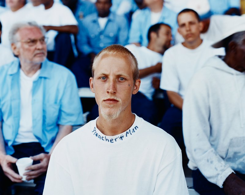 "young man with blonde hair and goatee wearing white t-shirt with ""Preacher Man"" written on collar"
