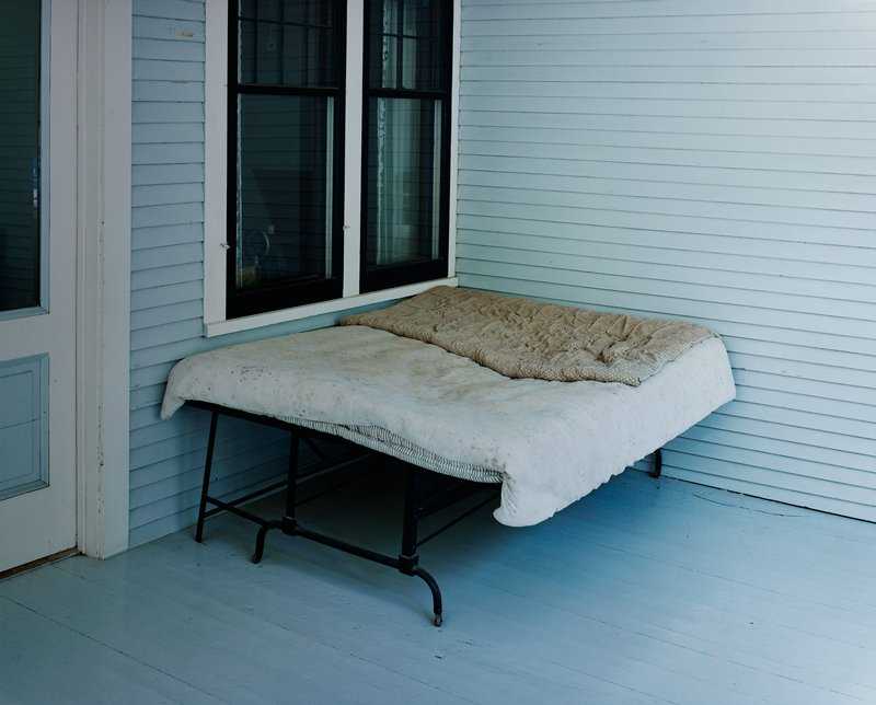 black metal cot with mattress and quilts on porch (?); blue, white and black paint; two windows