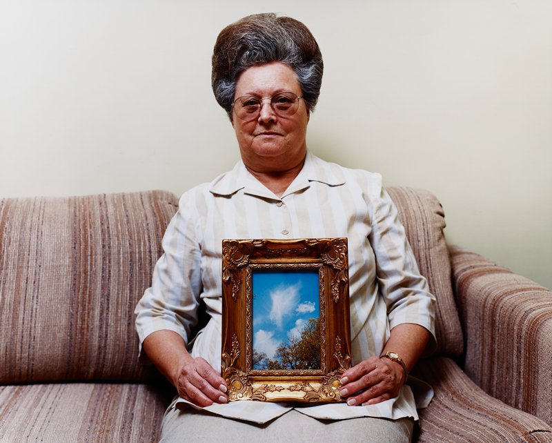 woman seated on couch holding photo in gold frame of angel-shaped cloud