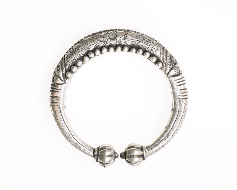 bracelet has sphere ends with ridges on them; a dragon extends from each sphere; dragon faces meet on the outer edges of the center of the bracelet; very center has a floral design and border of small spheres