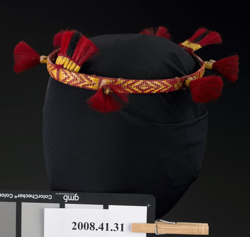 red and yellow fibers woven around circular band; six brush-like red elements; two tassel-like ornaments-one slightly larger than the other-front and back- with red and black hair