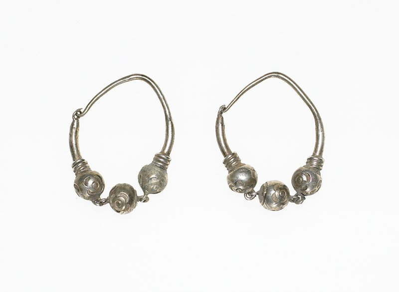 earrings have a loop of wire that connects to itself; at the center of the earring are three spheres with flowers on them, which are attached to each other with links