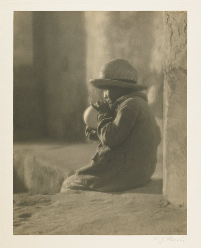 child seated on a ledge, wearing straw hat and heavy jacket, holding roughly spherical object to mouth; profile view