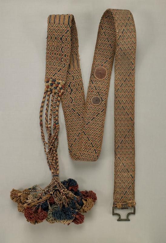 blue, tan, white, rust red and green, woven in zigzags and diamond motifs; braids with tassels at one end; buckle at opposite end; leather fragments