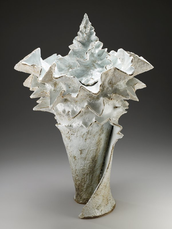 conical form, flaring outward toward top; conical cover; rolled design with zigzagging top edges and slightly spiraling zigzags on cover; milky white glaze with mottled brown areas; blue glaze at interior; rough surface