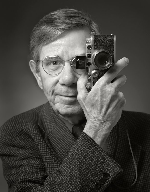 portrait of man wearing herringbone jacket and round glasses, holding a camera up to his PL eye