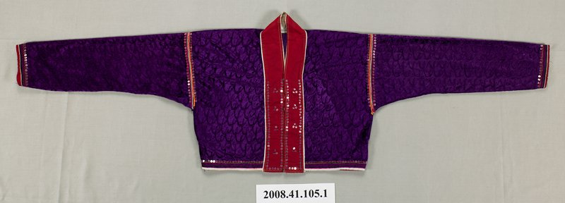 """short purple velvet jacket with dark red panel around neck and front opening; four snap closures on front; sequins around sleeve hems, lower edges of front and at sleeve seams; double row down front; 3"""" side band of green fabric attached to bottom edge of back has three rows of sequins and rows of embroidery in blue, red, yellow and white; bottom edges of back and sleeves bound in red fabric; front bound in white"""