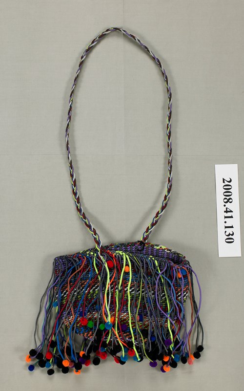 multicolored woven bag with attached multicolored small fabric balls; multicolored various length tassel fringe with balls on end; long braided fabric shoulder strap