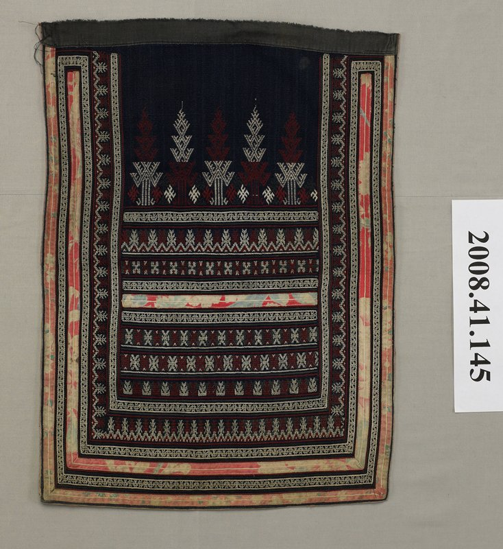 black panel with white, rust and grey embroidery; two strips of print fabric around edges separated by embroidery; one strip of fabric applied horizontally in center section; geometric designs