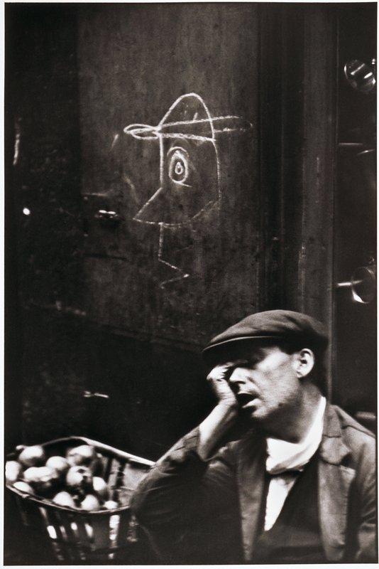 man with hand to his face, basket of apples and a chalk caricature of a man are behind him