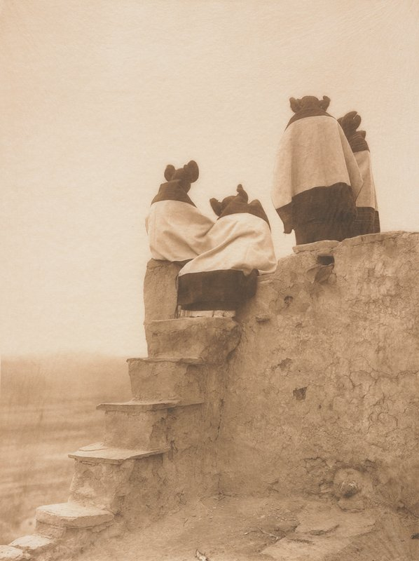 four girls, seen from back, with their hair in pairs of buns, wearing blankets over their shoulders, standing and seated on top of an adobe structure, with steps at left, looking down