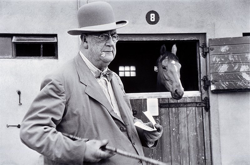 horse standing in stall number 8 with man carrying a cane in the foreground