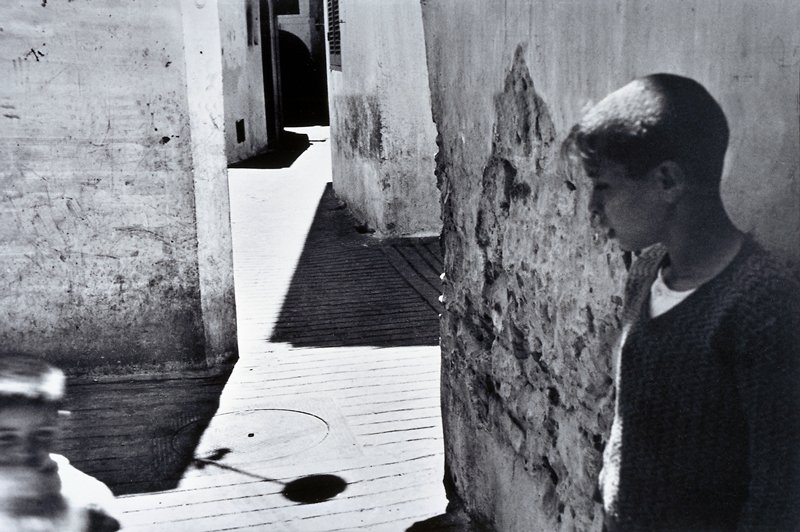 view looking down a winding, sunlit alley; two boys in foreground