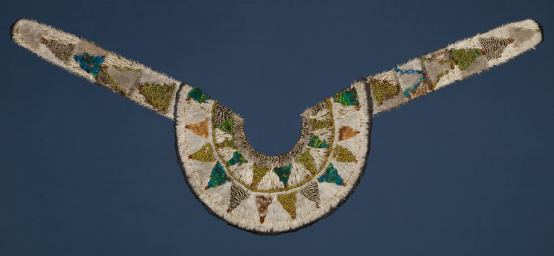 curved collar with two front downward-hanging tabs; feathers stitched to off-white cotton cloth backing overall; triangular motifs; background of cream and brown spotted feathers; brown, golden brown, spotted brown and white, iridescent blue-green and iridescent green, brown and yellow feathers
