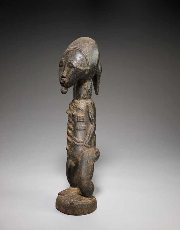 standing nude male figure with feet apart and short arms held closely to body; beard worn in small knob; hair in ponytail; slightly asymmetrical face with closed eyes; long, thick neck; scarifications on neck, body and between eyes and ears on sides of face; thick legs; dark brown patina