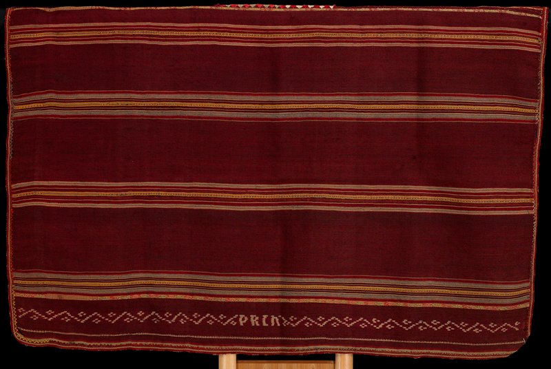predominantly rust colored with small stripes in purple, red, green, tan, yellow; several stripes have zigzag and scroll designs in white; ikat band at bottom on each side with zigzags, diamonds and letters (DACH?); green, red and white stitching at neck; striped trim; warp faced plain weave with complementary warp woven pattern bands and resist dye ikat patterning; heading band (?) sewn inside one side