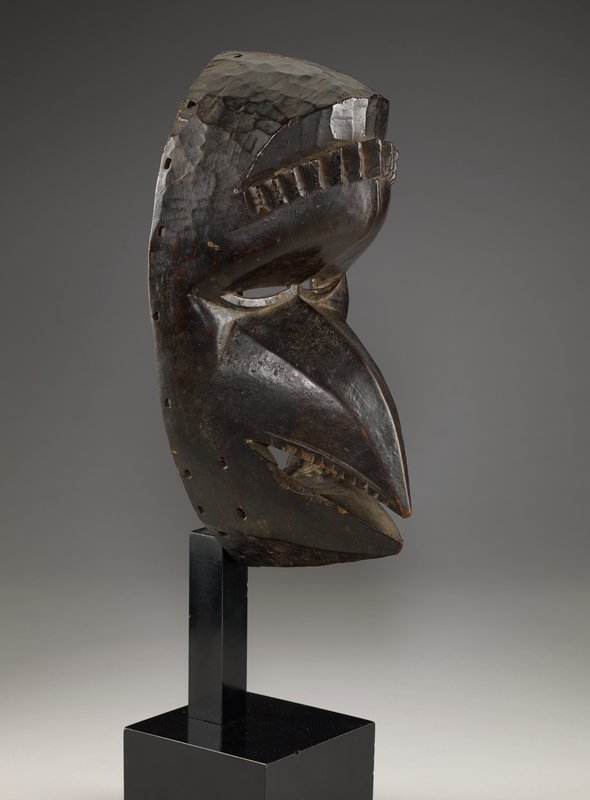 bird mask with short beak with teeth, narrow eye openings; curved row of small protrusions on forehead; top of head inherently rough; dark brown patina