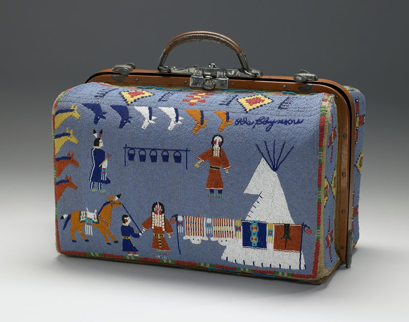 doctor bag-style with metal closure and metal handle; beaded overall with blue ground; geometric shapes on sides (crosses and triangles); one side has scene of two cowboys (one on white and black horse and one on rust-colored, white and yellow horse) roping blue and red steers; opposite side decorated with three Native American figures with teepee; horse in LLC and horses' heads around top and L sides; lined in light green