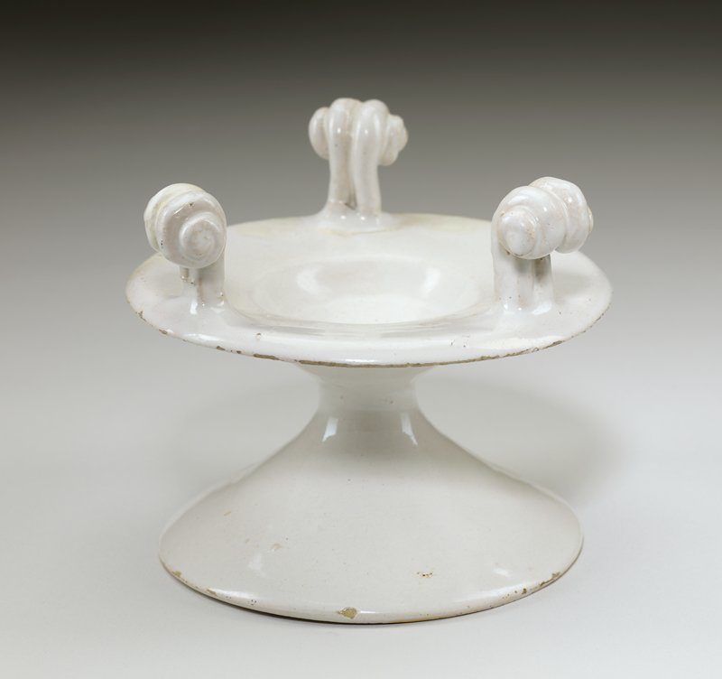 white; cone-shaped base; top has wide, downward-flaring rim and small central bowl; three vertical scrolls on top section