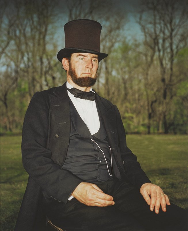 portrait of green-eyed, bearded man dressed as President Lincoln; man seated with hands resting on legs; silver watch chain attached to vest; gold ring on man's PL ring finger; blurry trees and blue sky in distance; framed behind glass in black wood frame; one of a set of 18 photographs to be displayed together