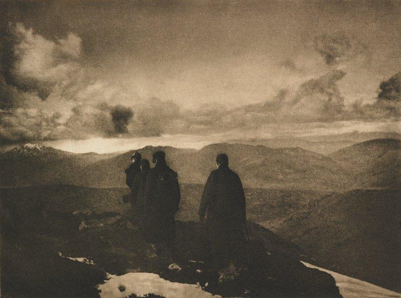 men hiking in mountains; dark composition