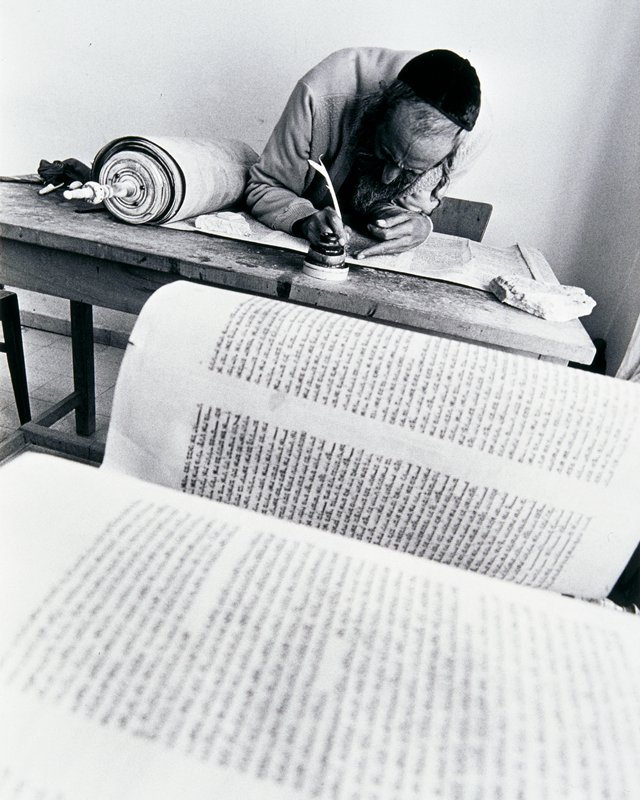 bearded man wearing a yarmulke bent over a scroll, writing, in background; pages of handwritten text in foreground