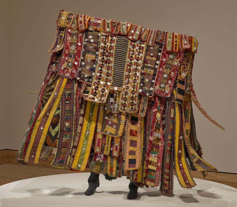 dress-like underbody; horizontal bar at top with doughnut-shaped section at center which rests on top of head; inset piece of knit blue and white material at top front (for wearer to see through); many vertical strips of various lengths of patchwork cloth trimmed in zigzags of colored felt and plastic; many different types of fabric--printed, velvet, pile, wool, felt; hammered aluminum pendants in various shapes scattered overall; some fabrics printed with text on back