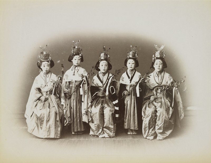 five girls--two standing between three seated on chairs; each girl wears a metal headdress with a V-shaped element on top, kimono, and cape with embroidery; girls hold leaf fronds; girls also have two dots painted on their foreheads
