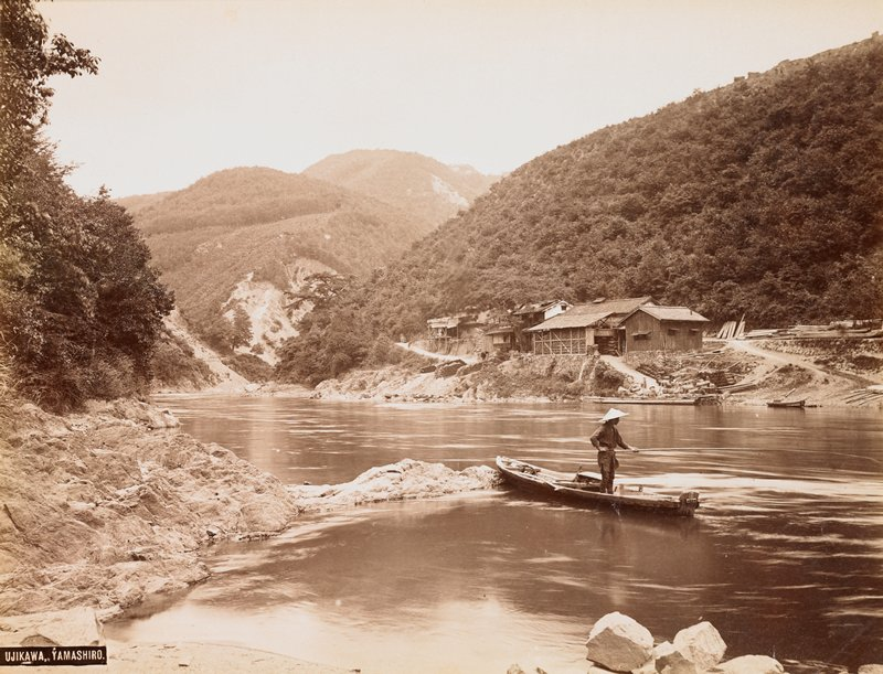 standing figure in a boat, wearing a straw hat and holding a very long fishing pole; rocky shoreline; buildings on far shore with tree-covered hillsides behind