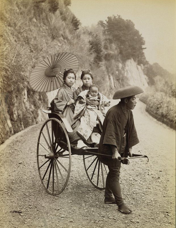 two women wearing traditional Japanese costumes, seated in a rickshaw; woman at left holds a parasol; woman at right holds a baby; man pulling rickshaw wears dark costume with short jacket and inverted bowl-shaped hat; view down a winding road with hills at left