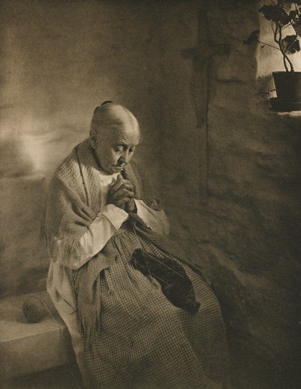 an older woman sits with hands folded in prayer, head bowed; she is inside stark room with single, visible window and a cross on the wall; knitting rests on her lap