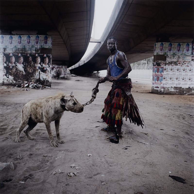 black man wearing a blue tank top and a predominately red checked skirt with leather streamers and tassels in green, cream, red and blue, and blue flip-flop sandals, holding a spotted hyena, wearing a muzzle attached to a heavy chain; man and hyena stand beneath large freeway ramps