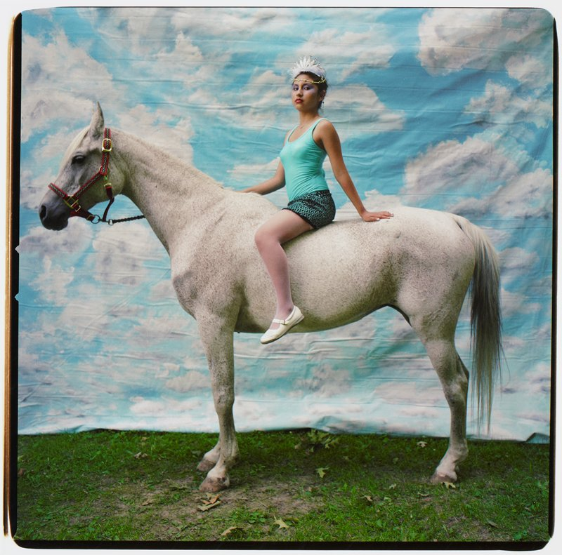 young woman wearing a turquoise tank top, turquoise and black skirt, white shoes and white beaded headdress, seated bareback on a white speckled horse, standing in front of a backdrop painted with blue sky and white clouds