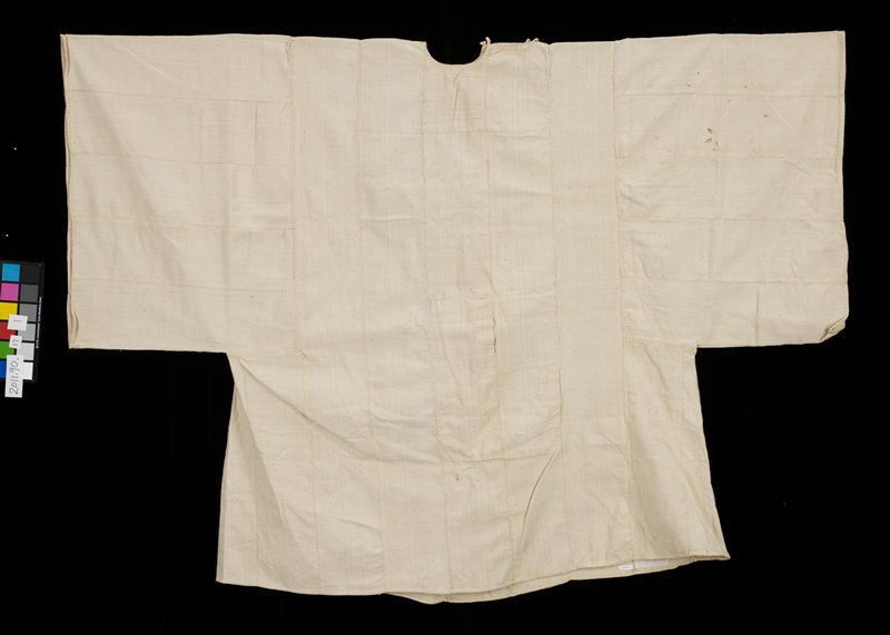"large off white/ivory shirt or jacket for daily wear; neck opening along shoulder seam; wide sleeves like kimono; made from strips of fabric approximately 6 "" wide; lengthwise strips for body with horizontal strips for sleeves; matching pants (see L2010.200.49.2); 2 panels (center); large reinforced area (sfront or back?)"