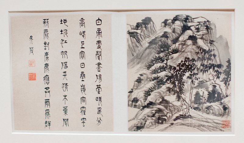 two album leaves mounted on boards and matted; left is calligraphic; right is landscape large mountain in center, two or three leafy trees at mountain base foreground, two buildings (?) behind them, other trees at right middle ground, other mountains upper left and right from accordion-style album, wood covers; eight images, alternating with text, single page of text at end