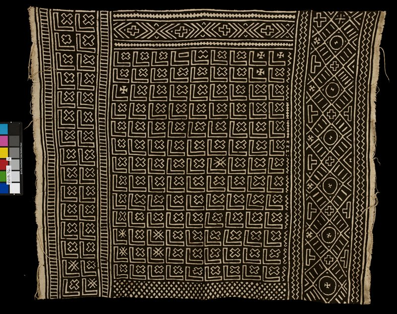 "black and tan textile; constructed of eight long strips stitched together; short edges have fringe; textile is decorated with the recurring symbols of an ""x"" and a line bent at a right angle; other designs that occur are crosses, chevrons, zig zags, and diamonds"