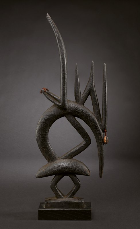 abstract animal shape; four legs; lozenge-shaped body; long horns and long pointed ears; one cowrie shell hanging from element on animal's forehead; maroon thread tassels at ends of ears; black patina; attached to dark wood base