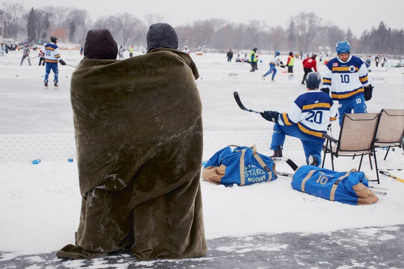 LON139191; caption: USA. Minnesota. Minneapolis. Winter Games. 2012.; color image of people playing outdoor ice hockey; pair of figures wrapped in olive green blanket stand to L of center, facing ice rink