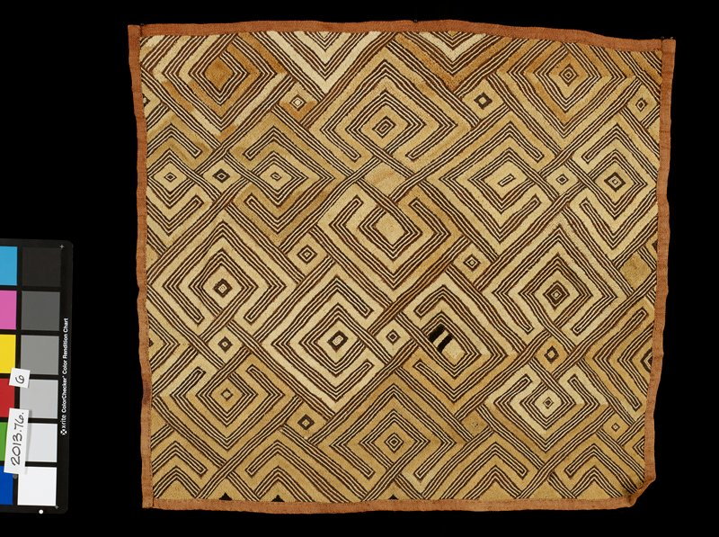 tan panel decorated with geometric tan and brown pattern; edges of panel are hemmed; geometric pattern is slightly raised