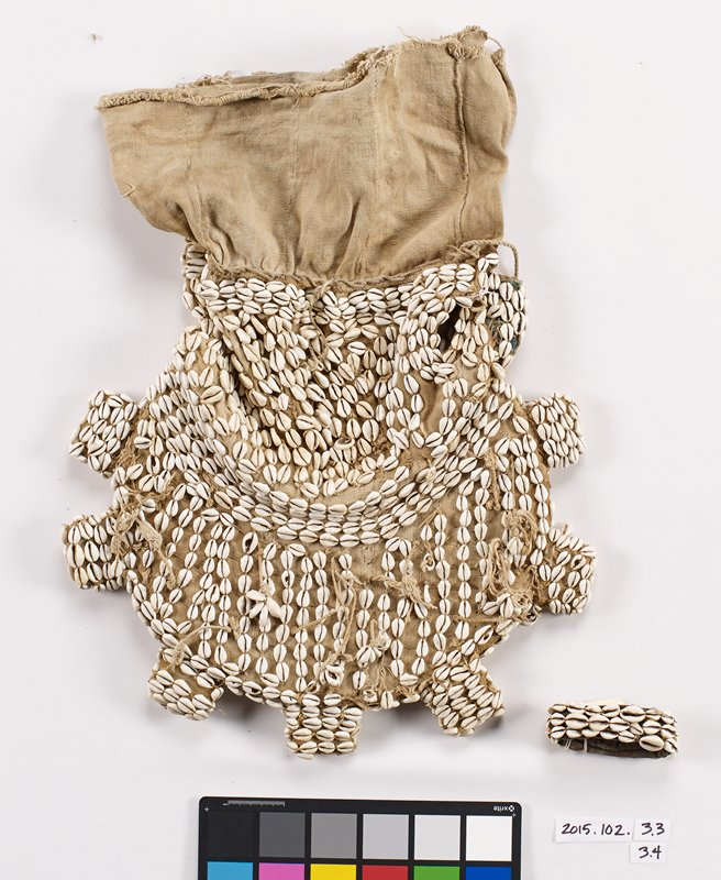 "cowrie shell covered headdress; tan fabric base covered with shells; 8"" strip of plain fabric at bottom; semicircular top portion; fabric is over board or cardboard; 7 protrusions on curved edge; eye and nose holes on one side; tassels with shells attached on top portion"