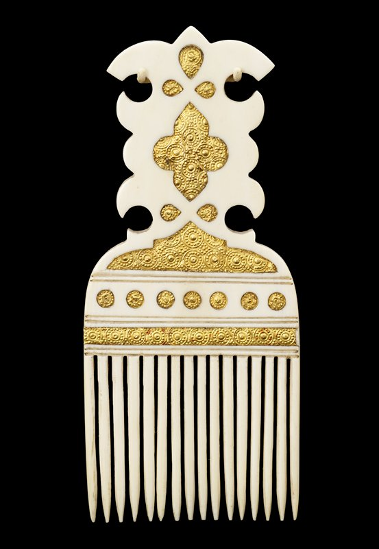 top decorated with symmetrical design with scrolling edges; some cutouts in various shapes (teardrops, circles, quatrefoil, bar) inlaid with gold stamped with repeating circular patterns on front and back of comb; tapering teeth