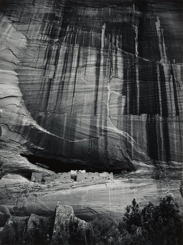 cliff dwellings with petroglyph of human form on rock wall below man-made walls; vertical streaking on rock wall above dwellings