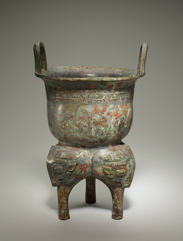 The decor of the upper part of this bipartite boiler is restricted to a neck belt with low, narrow flanges of which every second becomes the central ridge in the face of a dragonized t'ao-t'ieh,the halves formed by winged dragons.The bulbs of the Li-ting forming the lower half of the vessel are adorned with forceful t'ao-t'ieh heads of a fairly realistic bovine type, with eyebrows, ears, scaly horns .