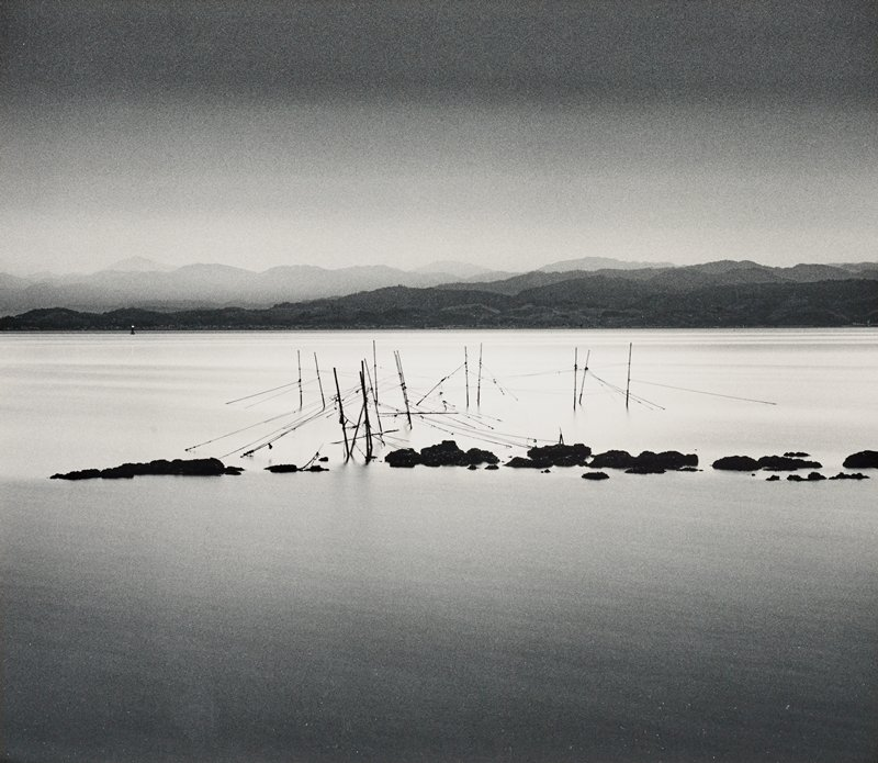 linear silhouettes of poles in calm water at center beyond lines of rocks; mountains in background