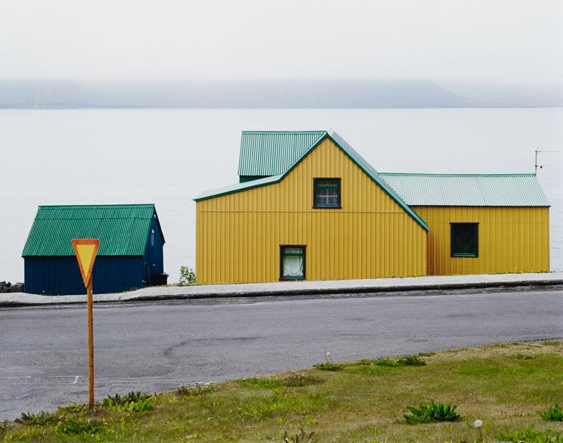 yellow house with green roof next to blue garage with green roof; water behind; road in front; triangular orange and yellow road sign on orange pole in LLQ